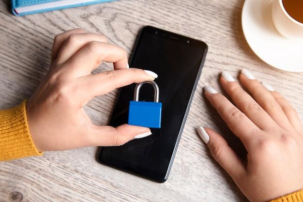 Mulher segurando a fechadura do telefone na mesa
