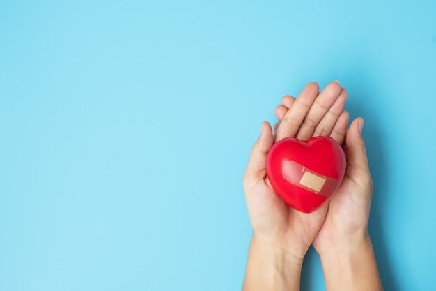 Mulher segurando a forma de coração vermelho sobre fundo azul. conceito de cuidados de saúde, seguro de vida, saúde e dia mundial do coração