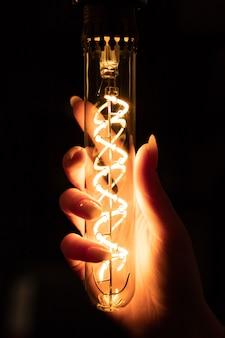 Mulher segurando a lâmpada de vidro longo fino brilha com grande espiral decorativa no escuro.