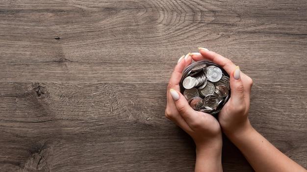 Mulher segurando a lata com moedas de metal