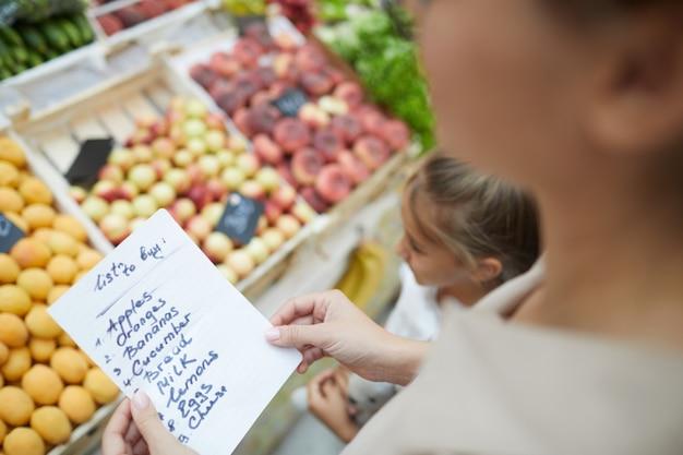 Mulher segurando a lista de compras closeup
