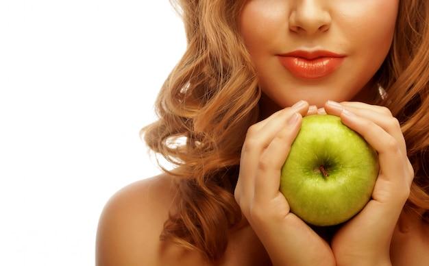 Mulher segurando a maçã verde.