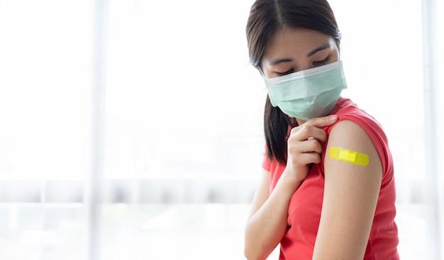 Mulher segurando a manga da camisa e mostrando o braço com bandagem após ser vacinada.