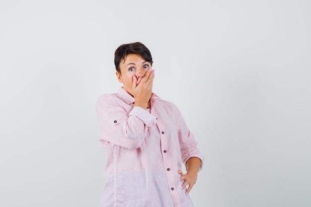 Mulher segurando a mão na boca em uma camisa rosa e parecendo surpresa. vista frontal.