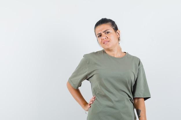 Mulher segurando a mão na cintura com uma camiseta e parecendo triste