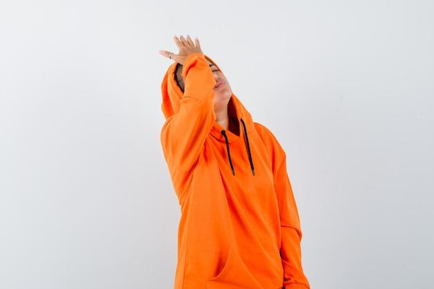 Mulher segurando a mão na testa com um capuz laranja e parecendo esquecida