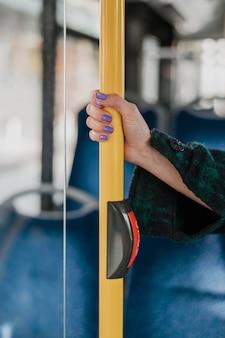 Mulher segurando a mão no poste do ônibus