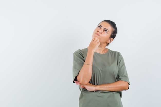 Mulher segurando a mão no queixo com uma camiseta e olhando pensativa