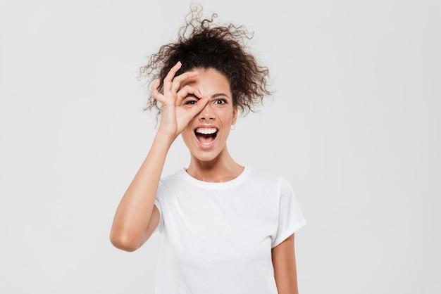 Mulher segurando a mão no rosto a rir e mostrando sinal okey