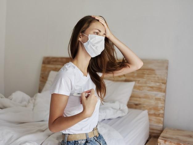 Mulher segurando a mão no termômetro da testa na máscara médica de mãos