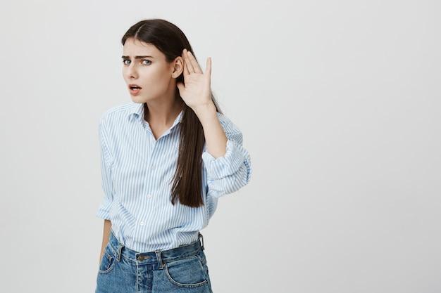 Mulher segurando a mão perto do ouvido não consegue ouvir nada