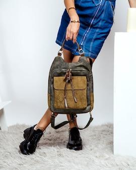 Mulher segurando a mochila de couro cáqui