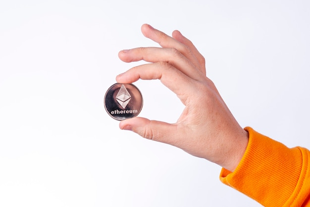Mulher segurando a moeda ethereum física (eth). conceitos de criptomoeda em fundo branco.