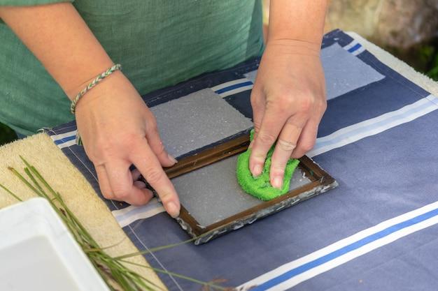 Mulher segurando a moldura para fazer folhas de papel de polpa de papel residual. foco seletivo. arte decorativa e aplicada. conceito de reciclagem, ecologia.