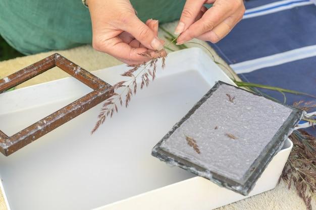 Mulher segurando a moldura para fazer folhas de papel de polpa de papel residual.
