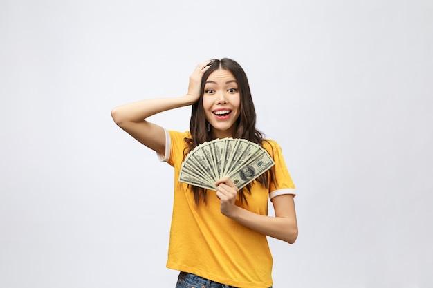 Mulher segurando a nota de dinheiro do banco. modelo muito jovem mostrando dinheiro Foto Premium