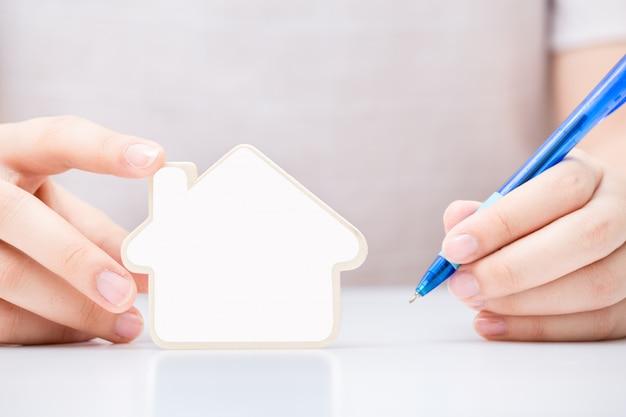 Mulher segurando a pequena casa com branco em branco sobre o documento
