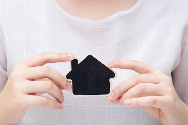 Mulher segurando a pequena casa. conceito para negócios imobiliários.