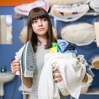 Mulher segurando a roupa e ferro de passar roupa
