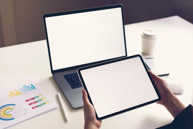 Mulher segurando a tela do tablet em branco e laptop em cima da mesa para promover seus produtos. da internet do futuro e da tendência para facilitar o acesso à informação.