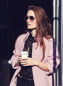 Mulher segurando a xícara de café branca