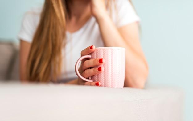 Mulher segurando a xícara de café na borda do sofá