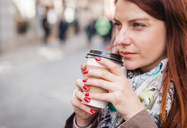 Mulher segurando a xícara de café na rua turva. tarde ensolarada de primavera. manicure vermelho. mão feminina com copo de papel de café levar embora.