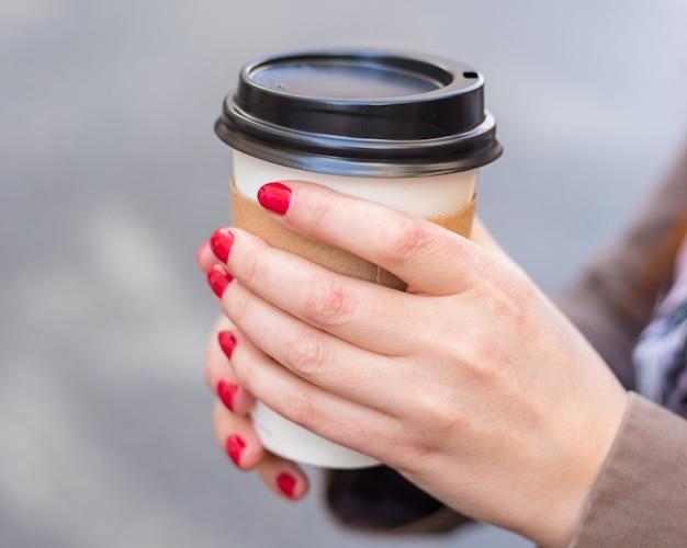 Mulher segurando a xícara de café na rua turva