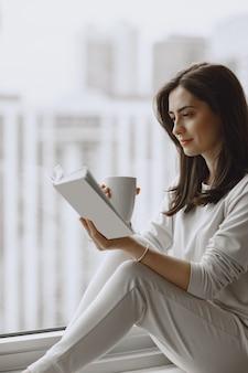 Mulher segurando a xícara de café.
