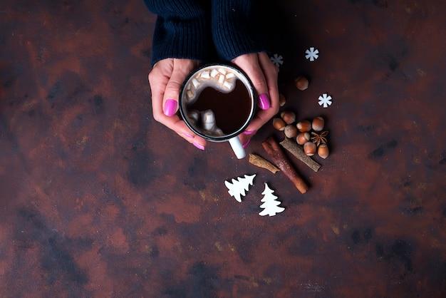 Mulher segurando a xícara de chocolate quente.