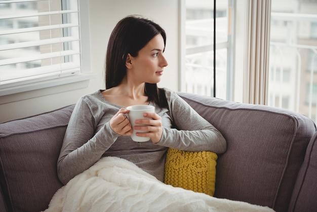 Mulher segurando a xícara enquanto olha pela janela