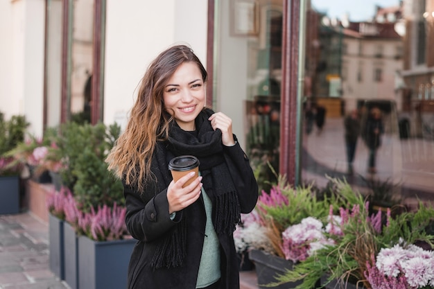 Mulher segurando a xícara no meio urbano