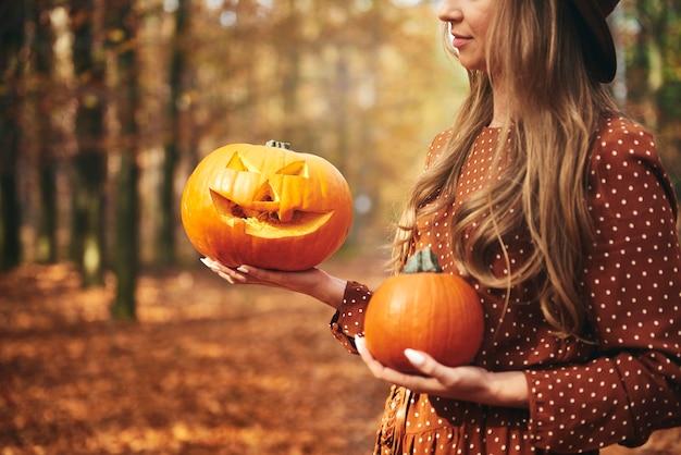 Mulher segurando abóbora de halloween na floresta de outono