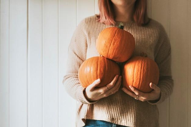 Mulher segurando abóboras de halloween em uma casa de fazenda