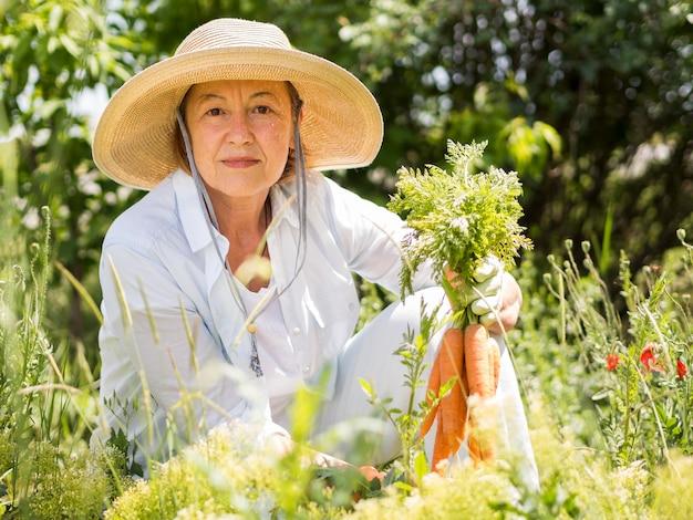 Mulher segurando algumas cenouras frescas na mão