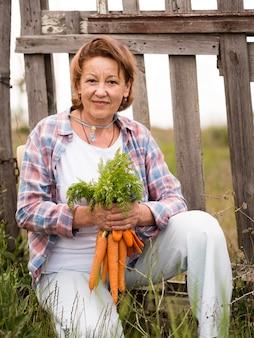 Mulher segurando algumas cenouras na mão