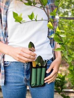 Mulher segurando algumas ferramentas de jardinagem