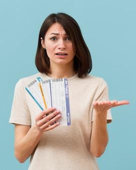 Mulher segurando alguns bilhetes de avião, olhando preocupado