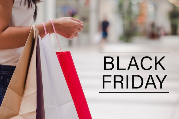 Mulher segurando alguns sacos de compras em pé no shopping. imagem horizontal.