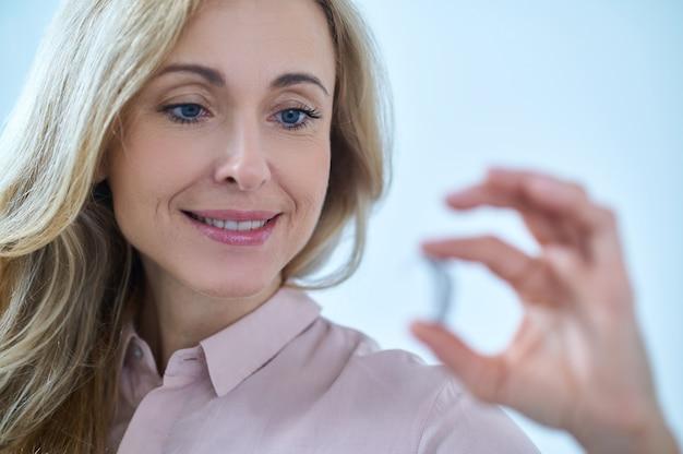 Mulher segurando aparelho auditivo nos dedos