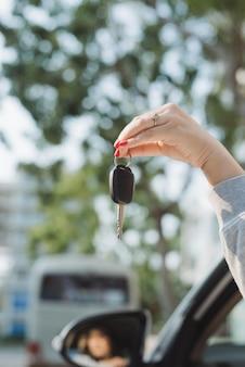 Mulher segurando as chaves de ignição de um carro na mão balançando-as pela janela lateral aberta