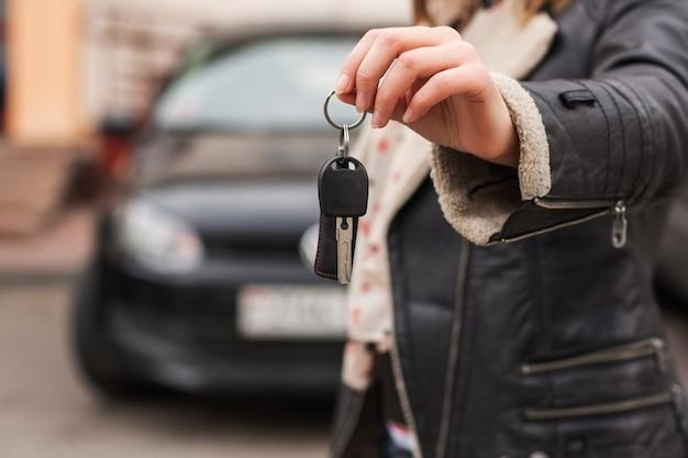 Mulher segurando as chaves do carro na frente de um carro