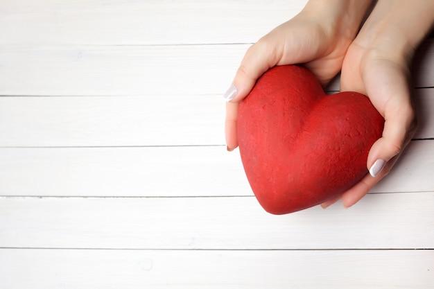 Mulher segurando as mãos coração vermelho sobre fundo branco de madeira, vista superior