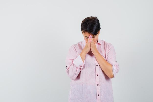 Mulher segurando as mãos em gesto de oração na camisa rosa e olhando esperançosa, vista frontal.