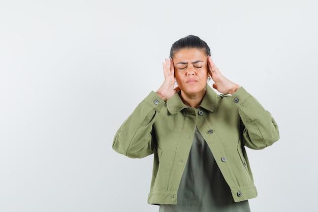 Mulher segurando as mãos nas têmporas em jaqueta, camiseta e parecendo exausta.