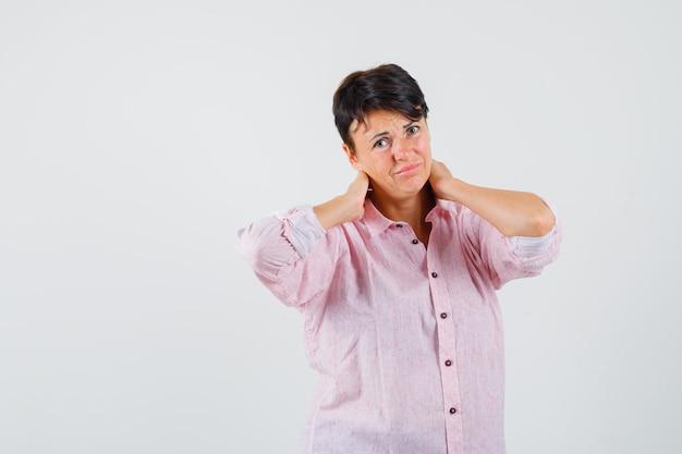Mulher segurando as mãos no pescoço em uma camisa rosa e olhando desesperada, vista frontal.