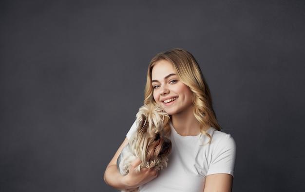 Mulher segurando as mãos pequeno cachorro de raça pura amizade abraço alegria fundo cinza