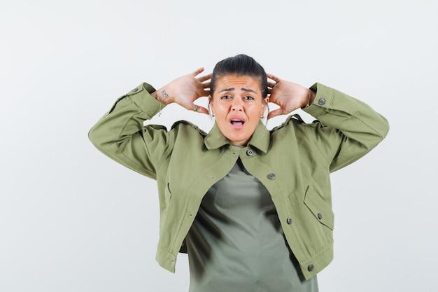 Mulher segurando as mãos perto da cabeça com jaqueta, camiseta e parecendo confusa.