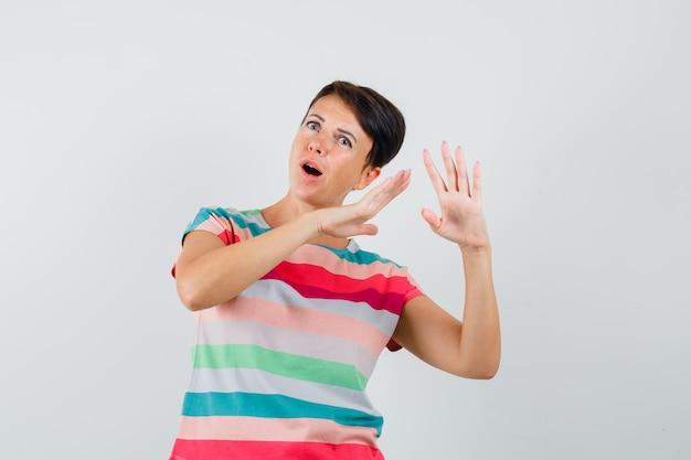 Mulher segurando as mãos perto das orelhas em uma camiseta listrada e olhando curiosa, vista frontal.