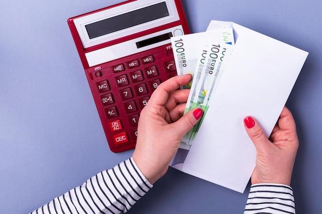 Mulher segurando as mãos segurando um envelope com dinheiro, calculadora, notas de euro.